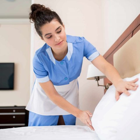 Pretty young professional chamber maid putting white clean pillows while bending over bed in hotel room