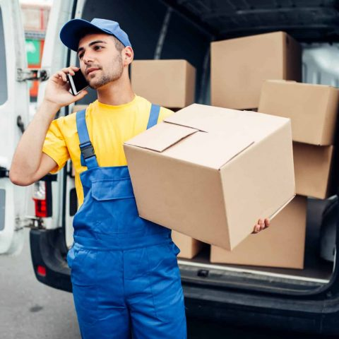 Cargo delivery service, male courier in uniform with box and mobile phone in hands. Empty container