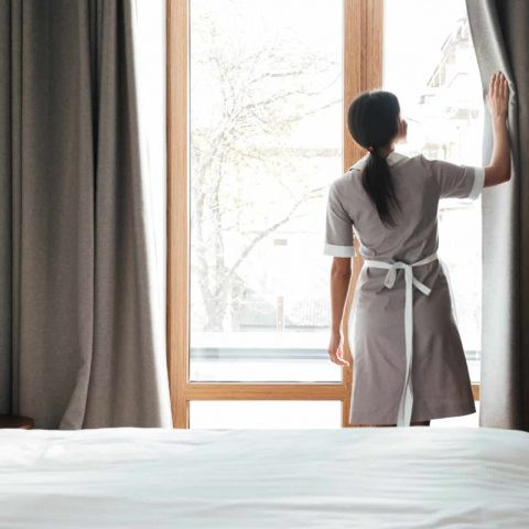 Female housekeeping opening window curtains in the hotel room