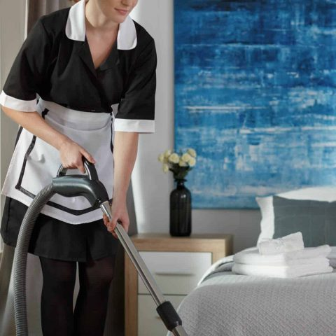 A housemaid in black and white dress vacuuming in the bedroom